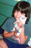 My familiar as a bottle fed kitten. (With my daughter.)